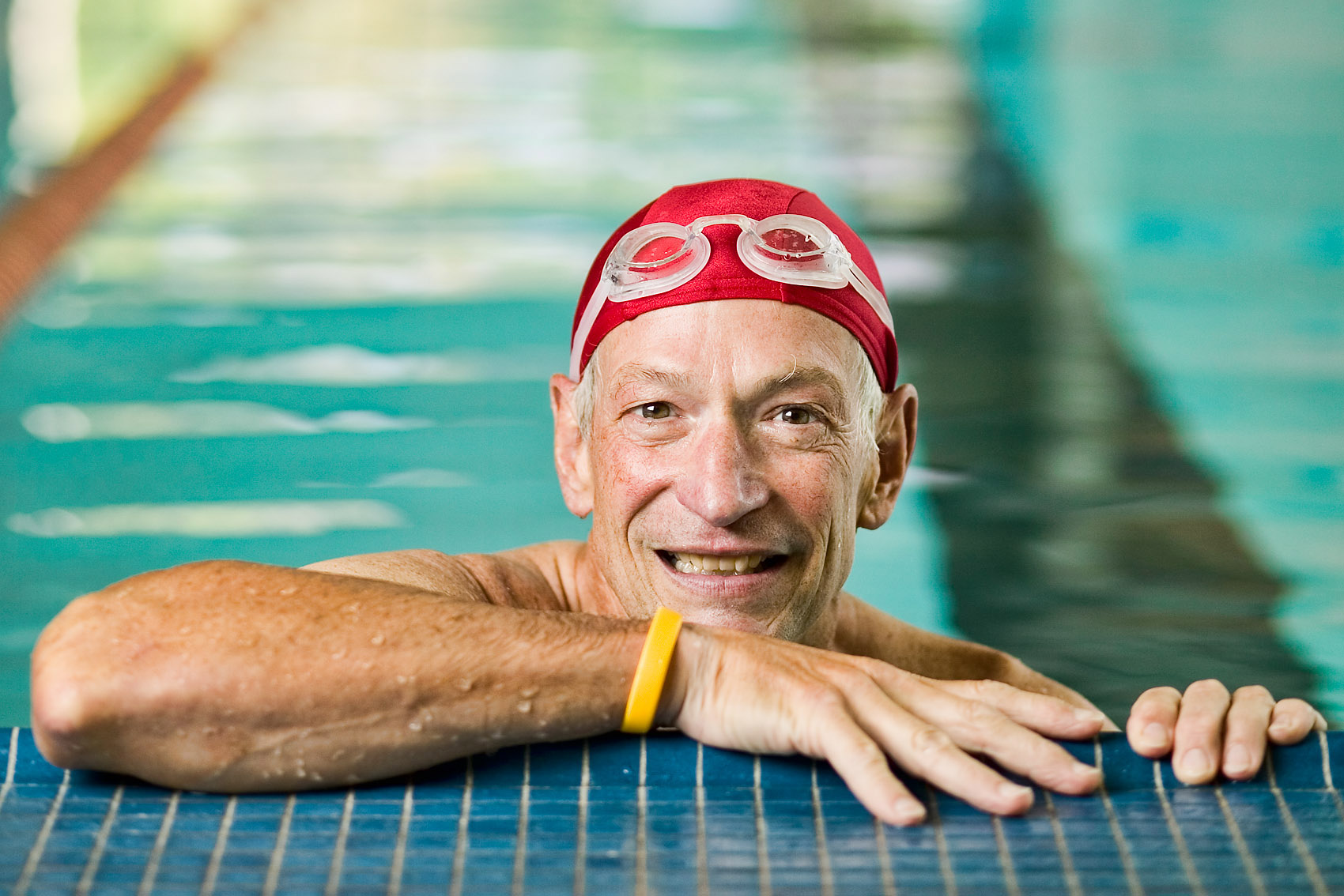 elderly man in red swim cap in the pool.