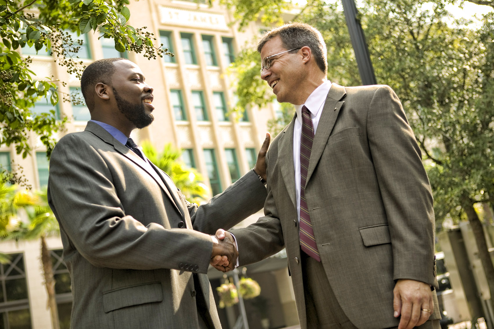 business executives friendly handshake outdoors